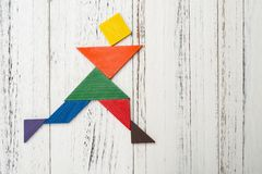 Wooden tangram shaped like a people skating on white. With copy space Stock Image