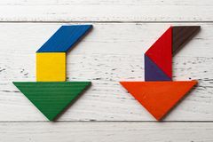Wooden tangram in two going down arrow shape Stock Photo