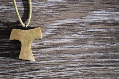 Wooden Tau Pendant. Wooden Christian Tau pendant on the wooden floor Stock Image