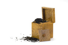 Wooden tea-caddy and scattered tea Stock Images