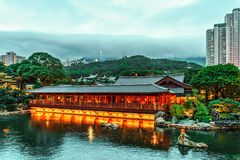 Wooden tea restaurant by pond in Nan Lian Garden at Diamond Hill in Hong Kong. Scenic twilight cityscape. Hong Kong, China - January 22, 2016: Wooden tea stock images