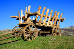 Wooden telega. Wooden cartage vehicle on green field in mountains Stock Photos