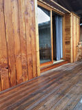 Wooden terrace and cladding. Cladding and wooden deck of a mountain chalet with bay window Royalty Free Stock Photo