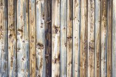 Wooden texture background in vertical brown laths and knotholes. The pattern consists of wood aged by weather. The handmade construction has warm colors and is Stock Photos