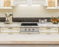 Wooden textured table over blurred kitchen stove interior background royalty free stock photos