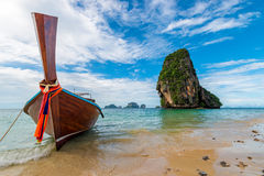 A wooden Thai boat with a motor on the background of a high clif. F in the Andaman Sea Royalty Free Stock Photo