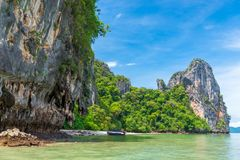A wooden Thai boat near an empty sandy beach on a tropical uninh. Abited beautiful island Royalty Free Stock Photography
