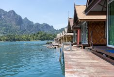 Wooden Thai traditional floating houses on a lake with mountains and rain forest in the background during a sunny day at royalty free stock image