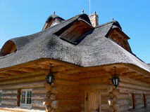 Wooden thatched house - close up. The old wooden house detail. Junction made without nails. Lamp hanging from a hook on the roof Stock Photos