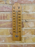 Wooden Thermometer. Wood thermometer on a brick wall, showing the temperature in degrees Celsius and Fahrenheit Stock Image
