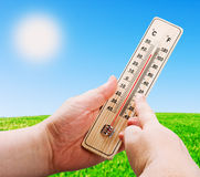 Wooden thermometer in hand Stock Photo