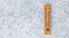 Wooden thermometer showing low temperature laying on flat ice ground made of crystals. Winter weather concept royalty free stock images