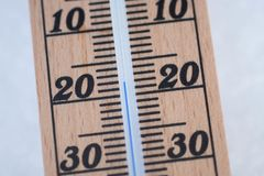 Wooden thermometer in snow with freezing temperature stock photography