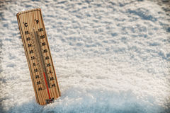 Wooden Thermometer in the snow with freezing temperatures stock photos