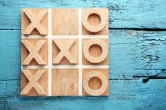 Tic tac toe game. Wooden tic tac toe game on blue table Stock Image