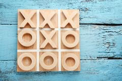 Tic tac toe game. Wooden tic tac toe game on blue table Royalty Free Stock Photo