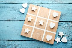 Tic tac toe game. Wooden tic tac toe game on blue table Stock Photo
