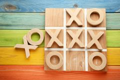 Tic tac toe game. Wooden tic tac toe game on colourful table Stock Photos