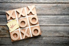 Tic tac toe game. Wooden tic tac toe game on grey table Royalty Free Stock Images