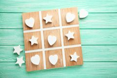 Tic tac toe game. Wooden tic tac toe game on mint table stock image