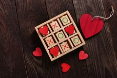 Tic tac toe game with hearts and xo letters as love game concept. Wooden tic tac toe game with red hearts and letters XO as love game concept for valentine`s day stock image
