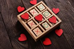 Tic tac toe game with hearts and xo letters as love game concept. Wooden tic tac toe game with red hearts and letters XO as love game concept for valentine`s day royalty free stock image