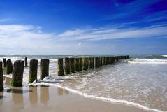 Wooden tidal breakwater. Scenic view of wooden posts forming tidal breakwater on beach with blue sky and cloudscape background Stock Photos