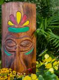 Wooden tiki head with carved features and painted accents surrounded by flowers and tropical greenery - selective focus stock image