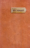 Wooden Toilet Sign. Wooden Toilet Sign on The Orange Wall Stock Photo
