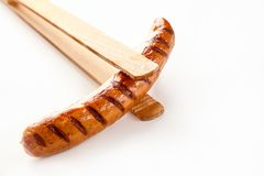 Wooden tongs holding a cooked, seared sausage. Wooden tongs holding a cooked, seared, barbecued sausage on a white background with copy space stock images