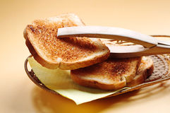 Wooden tongs and toast Stock Images