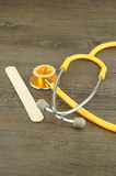 Wooden tongue depressor and stethoscope Royalty Free Stock Photography