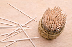 Wooden toothpicks from above on a cutboard. Wooden toothpicks in round wattled straw holder stock image