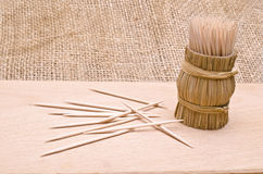 Wooden toothpicks on a cutboard. Wooden toothpicks in round wattled straw holder Royalty Free Stock Photography
