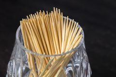 Wooden toothpicks in a glass Cup are on the table, on a dark background. oral hygiene after eating royalty free stock images