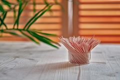 Wooden toothpicks stand on wooden. Table. On a background of a window and green twig plant. e view Stock Photo