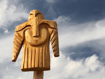 Wooden totem pole. Wooden totem idol pole with cloudy sky as a background Royalty Free Stock Images