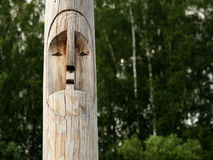 Wooden totem pole. Wooden totem idol pole with a forest as a background Royalty Free Stock Images