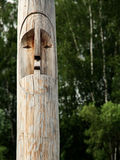 Wooden totem pole. Wooden totem idol pole with a forest as a background Stock Photos