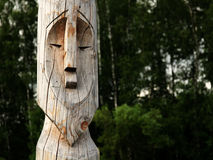 Wooden totem pole. Wooden totem idol pole with a forest as a background Royalty Free Stock Photos