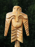 Wooden totem pole. Wooden totem idol pole with a forest as a background Stock Photo