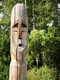 Wooden totem pole. Wooden totem idol pole with a forest as a background Royalty Free Stock Photo