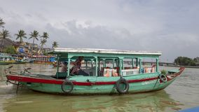 Wooden tour boat, teal color with red trim, on the Thu Bon river in Hoi An, Vietnam. Pictured is a wooden tour boat, teal color with red trim, on the Thu Bon stock photo