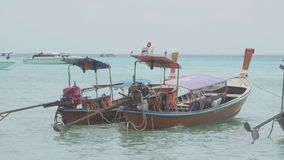 Wooden tour boat. tied on a pristine. white sand. tropical beach stock footage
