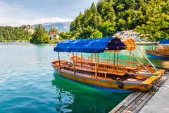 Wooden Tourist Boat on Shore of Bled Lake, Slovenia. With Bled Castle in Background Royalty Free Stock Photos