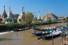 Wooden tourist boats and temples on Inle lake, Myanmar (Burma) Stock Images