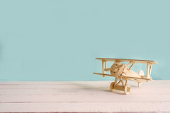 Wooden toy airplane against green background with copyspace royalty free stock photo