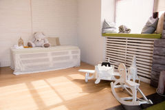 Wooden toy airplane and horses on the floor in the room. stock photo