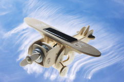 Wooden toy airplane with solar panel on  blue sky and cloud background Royalty Free Stock Photos