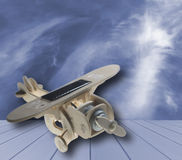 Wooden toy airplane with solar panel on blue wood, on  blue sky and cloud background Stock Photography